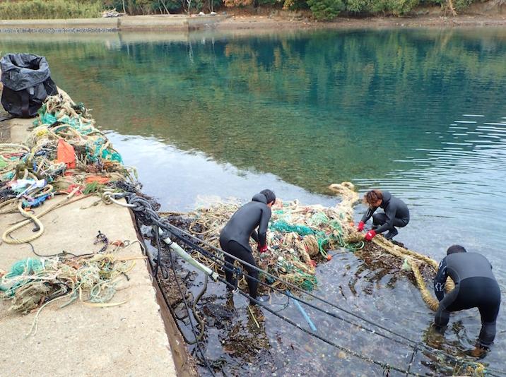 漁網やロープが絡まった漂着ごみの解体作業。既に半分以上は陸揚げされた状況です。